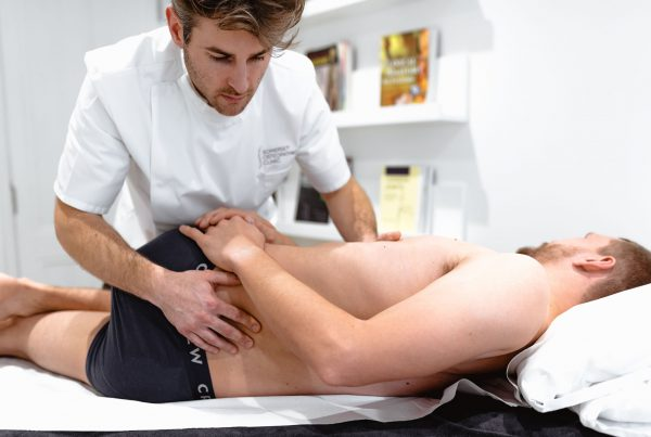 Osteopath treating a man with back pain