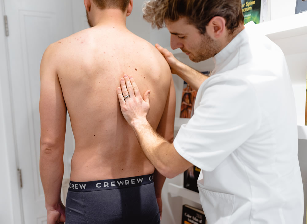 osteopath diagnosing back pain