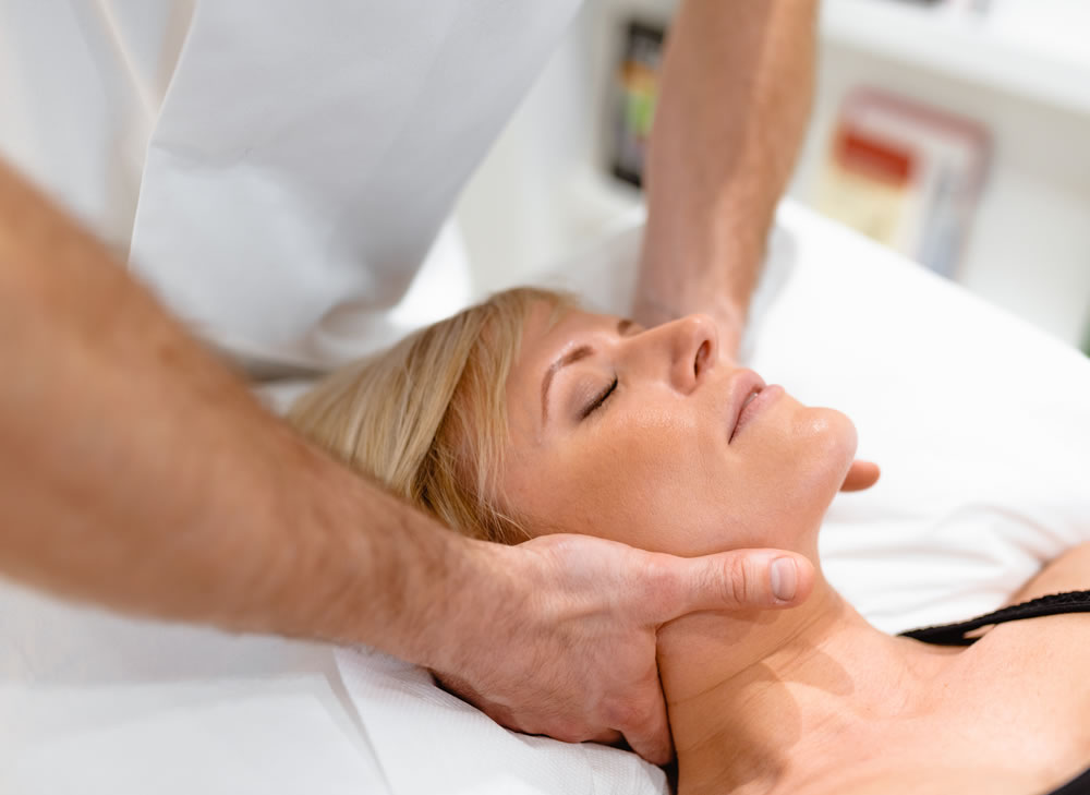 osteopath treating a woman with a headache