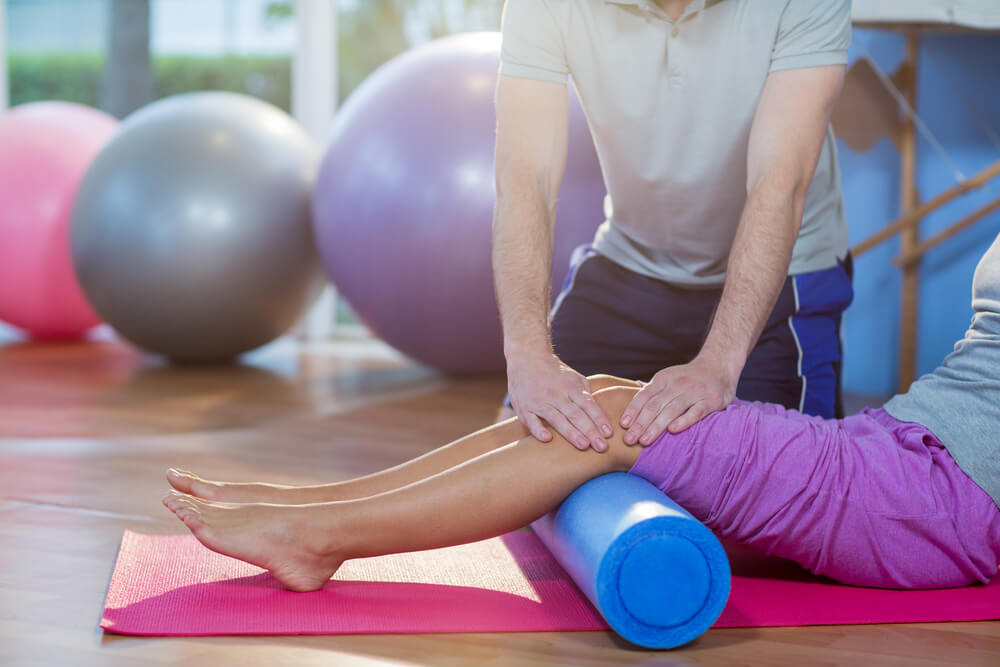 Pt instructor with a client exercising with a foam roller